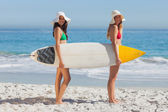 Two women in bikinis holding a surfboard — Stock Photo