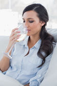 Relaxed pretty brunette drinking white wine sitting on sofa — Stock Photo