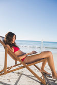 Woman using her laptop while relaxing on her deck chair — Stock Photo