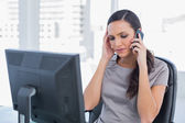 Dark haired businesswoman with headache having a phone conversat — Stock Photo