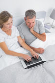 Thoughtful couple using their laptop together in bed — Stock Photo