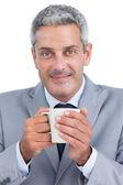 Content businessman holding mug — Stock Photo