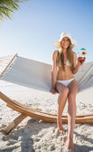 Cheerful blonde wearing bikini and sunhat sitting on hammock wit — Stock Photo