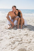 Cuddling couple smiling at camera sitting on sand — Stock Photo