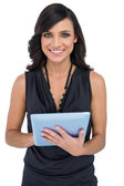 Smiling elegant brown haired model using tablet-computer — Stock Photo