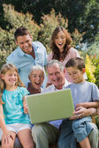 Happy multi generation family with a laptop sitting in park — Stock Photo