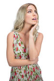 Pensive pretty blonde wearing flowered dress posing — Stock Photo
