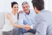 Woman shaking hands with salesman sitting beside husband — Stock Photo