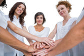 Cheerful models joining hands in a circle and looking at camera — Stock Photo