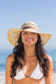 Attractive dark haired woman wearing straw hat posing — Stock Photo