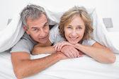Happy couple under the duvet — Stock Photo