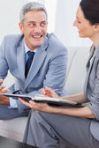 Cheerful business people working and talking together on sofa — Stock Photo