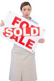 Estate agent showing for sale sign with sold sticker across it — Stock Photo