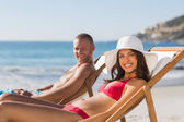 Young couple on their deck chairs smiling at camera — Stock Photo