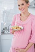 Happy expecting woman offering biscuits — Stock Photo