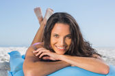 Smiling attractive brunette relaxing on her lilo — Stock Photo