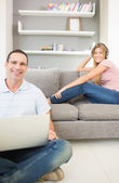 Man sitting on floor using laptop with woman listening to music — Stock Photo