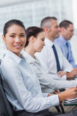 Cheerful employee attending presentation with her colleagues — Stock Photo