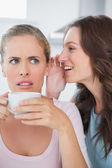 Woman telling secret to her friend while drinking coffee — Stock Photo