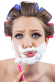 Curious model in hair curlers posing with shaving foam and razor — Stock Photo