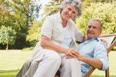 Szczęśliwy starsza kobieta siedzi na jej męża na leżak — Zdjęcie stockowe