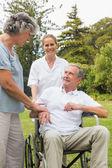 Счастливый человек в инвалидной коляске, разговор с женой и медсестра — Стоковое фото