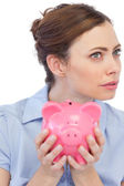 Thoughtful businesswoman posing with piggy bank in close up — Stock Photo
