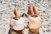 Sexy blonde and brunette wearing straw hat clinking their glass — Stock Photo