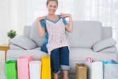 Smiling blond woman with shopping bags trying out a top — Stock Photo