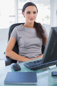 Serious businesswoman sitting on her swivel chair — Stock Photo