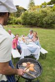 Happy extended family having a barbecue being cooked by father i — Stock Photo