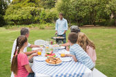 Cheerful extended family watching father at the barbecue — Stock Photo
