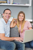 Cheerful couple sitting using laptop on the couch together — Stock Photo