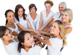 Female models joining hands in a circle and looking at camera — Stock Photo
