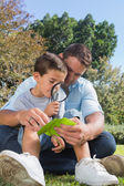 Smiling dad and son inspecting leaf with a magnifying glass — Stock Photo