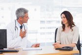 Serious patient talking with her doctor about illness — Stock Photo
