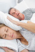 Tired wife blocking her ears from noise of husband snoring — Stock Photo