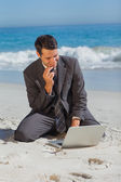 Young businessman sitting on the sand with his laptop — Stock Photo