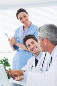Happy nurse listening to doctors talking about something on thei — Stock Photo