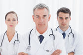 Serious doctors posing together crossing arms — Stock Photo