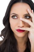 Thoughtful dark haired woman with red lips hiding her face — Stock Photo