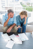 Worried couple sitting on their couch paying their bills — Stock Photo