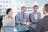 Serious business team interviewing experienced man — Stock Photo