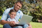 Usměvavý syn a otec s notebookem — Stock fotografie