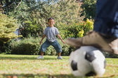 Son standing as goal keeper with dad — Stock Photo