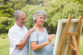 Peaceful retired woman painting on canvas with husband — Stock Photo