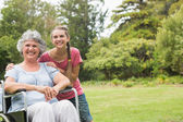Grandmother in wheelchair and granddaughter smiling into the cam — Stock Photo