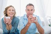 Conteúdo médio par envelhecido, sentado no sofá tomando café — Foto Stock