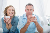 Content middle aged couple sitting on the couch having coffee — Stockfoto