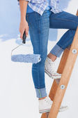 Woman holding paint roller climbing ladder — Stock Photo
